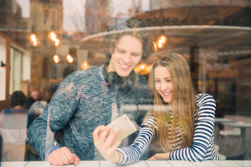 Beautiful, happy couple of students sits in a cafe and does selfie-photo inside