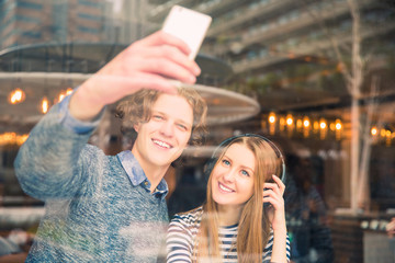 Attractive smiling couple sits in cafe and does selfie-photo, a woman listens to music in the earphones on her ears, indoors