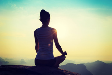 young fitness yoga woman meditating on sunrise mountain peak