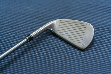 Close up shot of golf club on blue mat background.