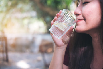 A woman holding and drinking cold water with blur nature background