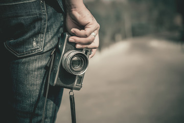 Man photographer holding a vintage camera.