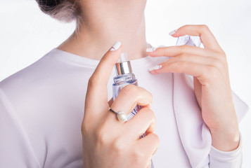 Woman applying perfume on her neck
