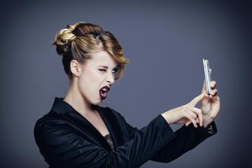 Portrait d'une jeune femme clignant de l'oeil, de profil, se prenant en photo avec son téléphone portable
