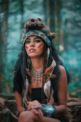 Futuristic indian woman portrait outdoors. Background blue wild forest