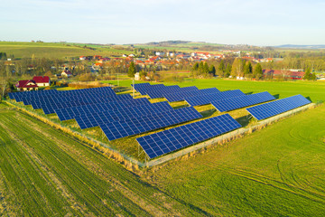 Aerial view of solar power plant. Photovoltaic power station supplying electricity to small town in countryside.