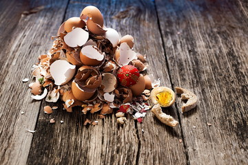 Broken eggshells on old farmhouse rustic wooden background after Easter holidays