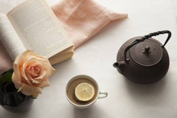 Teapot on a table with an open book and a white tea cup with lemon. Relaxing time.