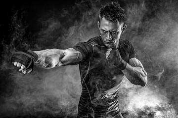 Studio portrait of fighting muscular man in smoke on black background Wall mural