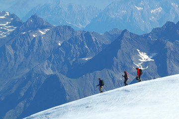 Group of walking Tourists on the glacier with mountains on background