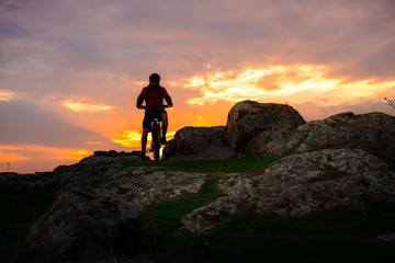 Silhouette of Cyclist with Mountain Bike on the Spring Rocky Trail at Beautiful Sunset. Extreme Sports and Adventure Concept.