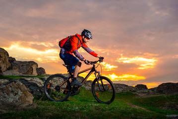 Cyclist Riding Mountain Bike on the Spring Rocky Trail at Beautiful Sunset. Extreme Sports and Adventure Concept.