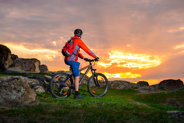Cyclist with his Mountain Bike Looking at the Beautiful Sunset on Spring Rocky Trail. Extreme Sports and Adventure Concept.