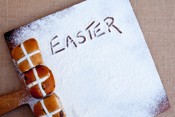 hot cross buns on floured wooden cutting board, with word Easter written in flour