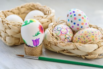 Decorate eggs for Easter. Easter eggs in a wicker basket on a wooden table