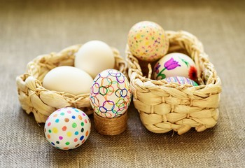 Easter eggs in a two wicker basket on the tablecloth of burlap