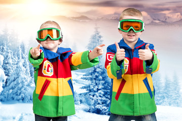 Two brothers of the boy snowboarder in bright ski jackets and goggles is skiing in the mountains.
