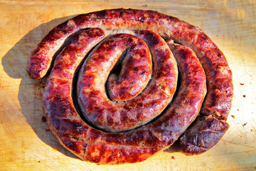 Delicious sausages on wooden plate cooked on barbecue grill