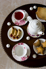 Karkade with sweets. Traditional family tea for three at a round table