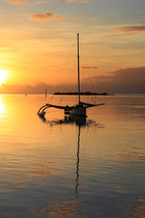 Silhouette of a sail boat at sunset at sea. Amazing colorful sunset on the beach of Moorea, French Polynesia.
