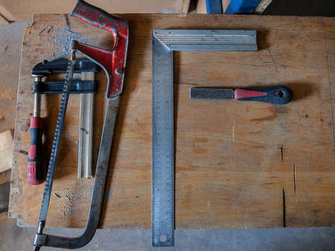 Woodworking tools (T Square, clamps, saw, and a file) put on a wooden workbench.