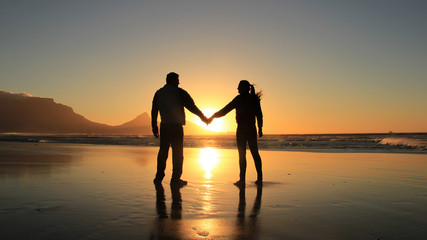 Concept of love and happiness. Silhouette of a romantic couple holding hands on the beach at Cape Town city, South Africa. Man and woman enjoying sunset on beach.