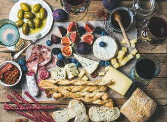 Wine and snack set with various wines in glasses, meat variety, ciabatta, sun-dried tomatoes, honey, green olives, figs, nuts and berries on wax paper over rustic wooden table background, top view