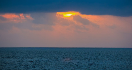 Orange sunset over the sea, rich in dark clouds and rays of light