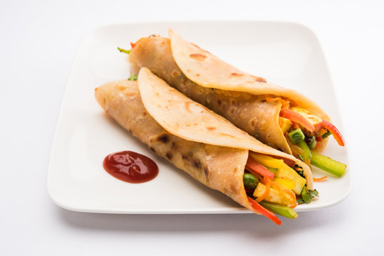 Indian popular snack food called Vegetable spring rolls or veg roll or veg franky made using paneer or cottage cheese and vegetables wrapped inside paratha/chapati/roti with tomato ketchup.