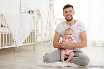 Father sitting with cute baby daughter on floor at home