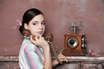 Stunning vintage 1920s woman talking on an antique telephone