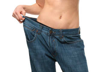 Diet concept. Young beautiful woman in large jeans on white background