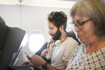 Denmark, Young woman, mid adult man and senior woman on plane