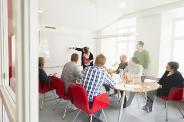 Sweden, Young woman drawing on white board during work meeting