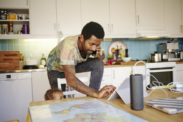 Sweden, Father with son (12-17 months) in kitchen, using mobile devices