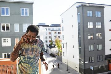 Sweden, Stockholm, Annedal, Mid adult man talking on smart phone on balcony