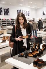 Sweden, Woman choosing shoes in shoe store