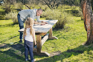 Finland, Paijat-Hame, Heinola, Father with daughter (4-5) polishing wooden table in garden