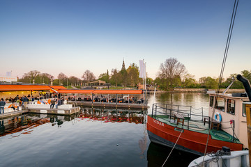 Sweden, Uppland, Stockholm, Djurgarden, Boats and restaurant on water with Nordic Museum in background