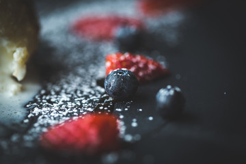 Macro photo of strawberry and Blueberries on slate plate with coconut background. Food concept. Red summer fruits. Close up object. Flare copy space for text, design