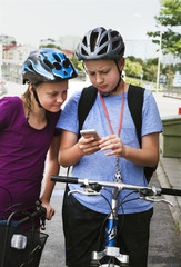 Sweden, Girl (10-11) and boy (12-13) with bicycles, using smart phone