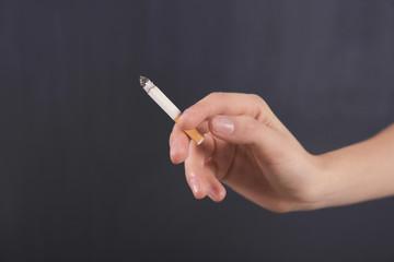 Female hand with cigarette on dark background