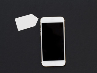 White phone with blank price label on black background. Smartphone with black screen banner template.