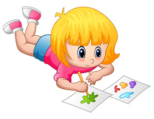 Little girl lying and painting on a paper