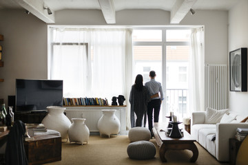 Germany, Couple looking through window in living room