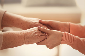 Old and young women holding hands on blurred background, closeup