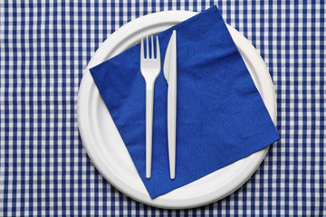 White plastic disposable tableware on napkin