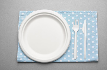 White plastic disposable tableware on gray background