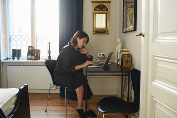 Sweden, Woman in black dress using laptop at home