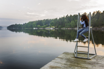 Sweden, Uppland, Roslagen, Vato, Woman sitting on ladder, photographing lake